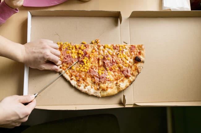 Man cutting pizza on carton box — Stock Photo