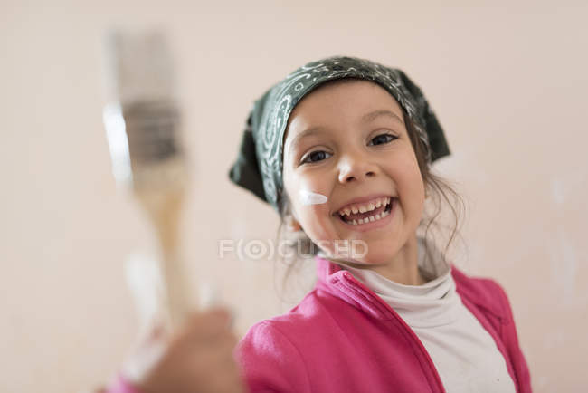 Happy little girl with paintbrush — Stock Photo