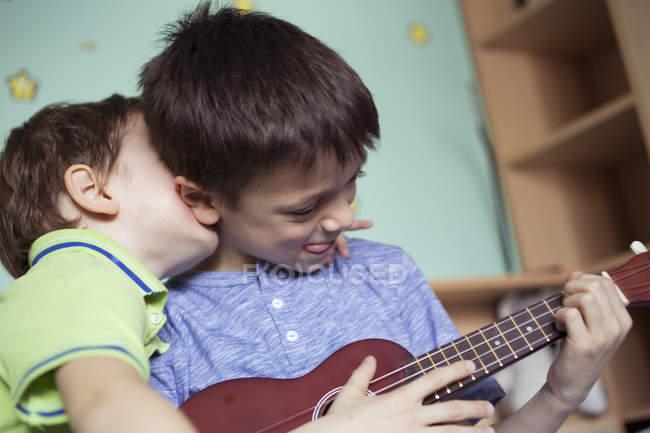 Boy playing ukulele while brother — Stock Photo