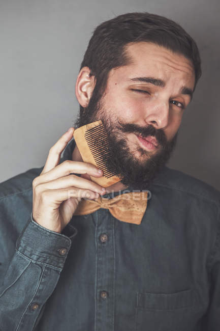 Man combing beard with wooden comb — Stock Photo