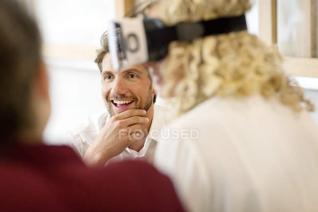 Blond woman trying out VR goggles at a workshop — Stock Photo