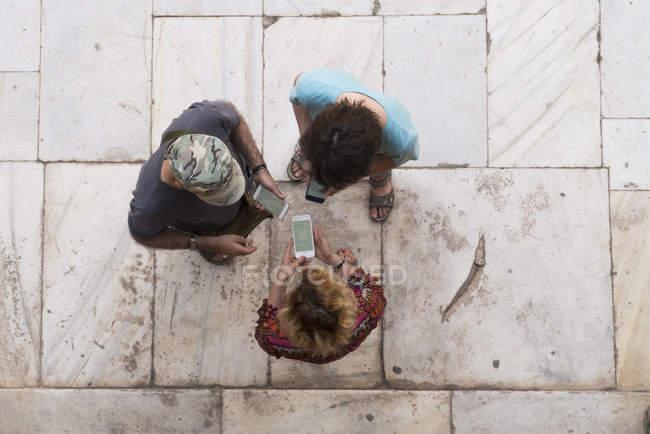 Три человека смотрят на мобильные телефоны — стоковое фото