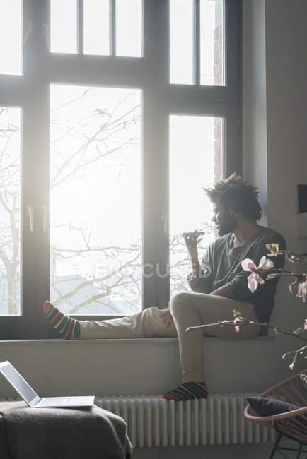 Uomo seduto sul davanzale della finestra — Foto stock