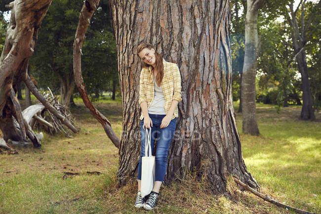 Jeune femme appuyé contre l'arbre — Photo de stock