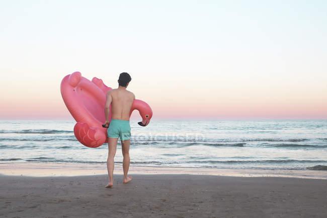 Hombre con inflable flamingo rosado - foto de stock