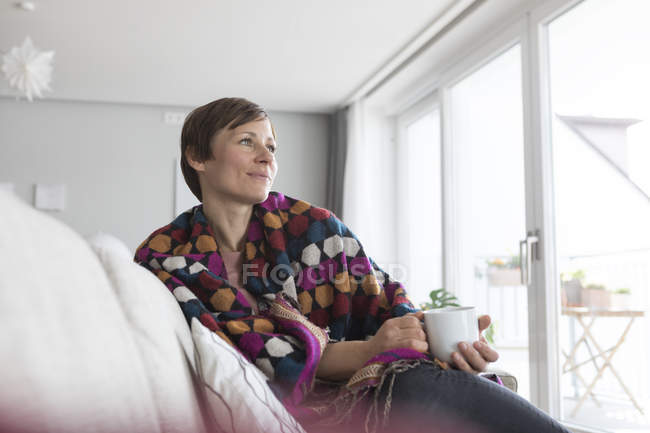 Woman with cup of coffee on couch — Stock Photo