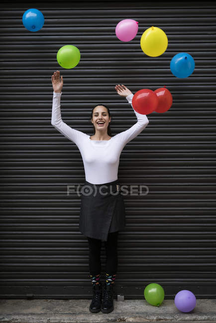 Woman standing with flying balloons — Stock Photo