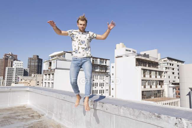 Barefoot man jumping from balustrade — Stock Photo