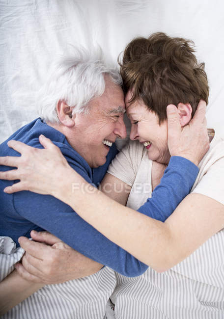 Senior Couple Hugging In Bed Stock Photo
