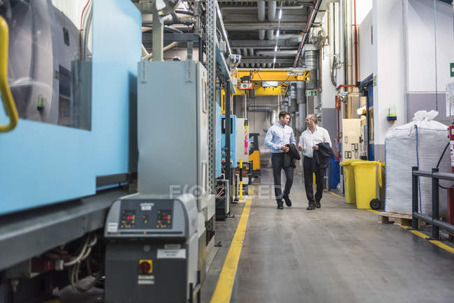 Two men walking and talking in factory — Stock Photo