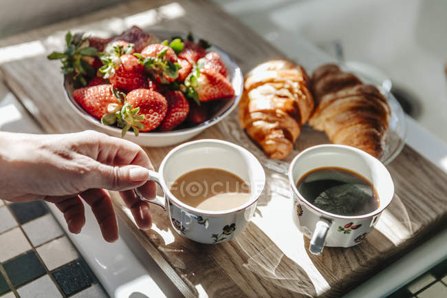 Hand taking cup of coffee — Stock Photo