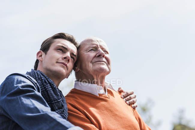 Старший чоловік і онук, сидячи на відкритому повітрі — стокове фото