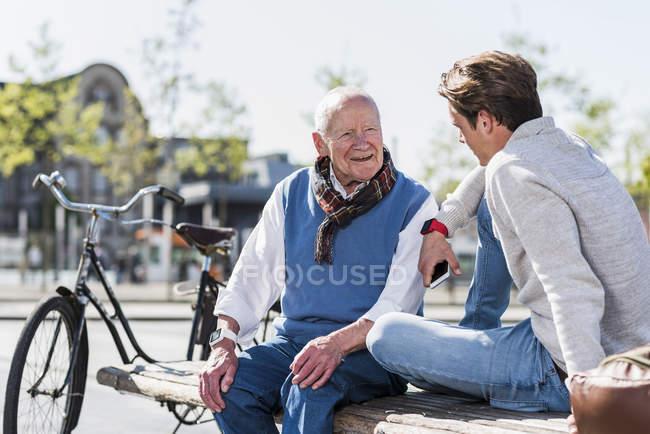 Старший чоловік і онук взаємодії на лавці — стокове фото