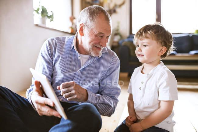Abuelo y nieto con tablet - foto de stock