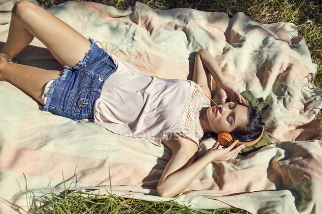 Woman on blanket listening to music — Stock Photo