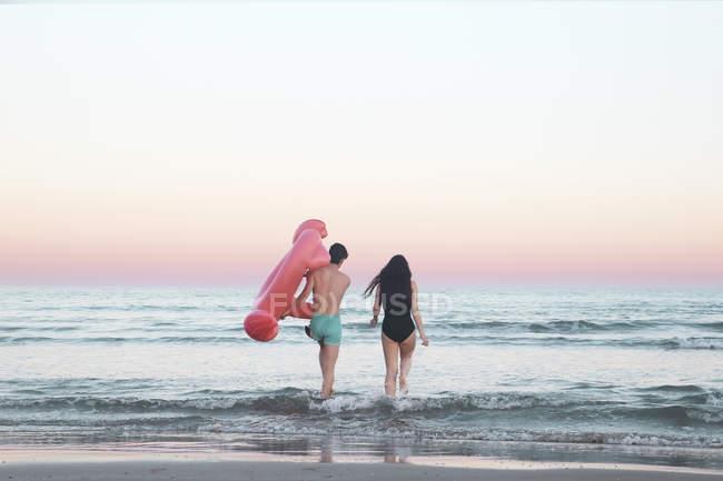 Pareja caminando en la mar con inflable flamingo - foto de stock
