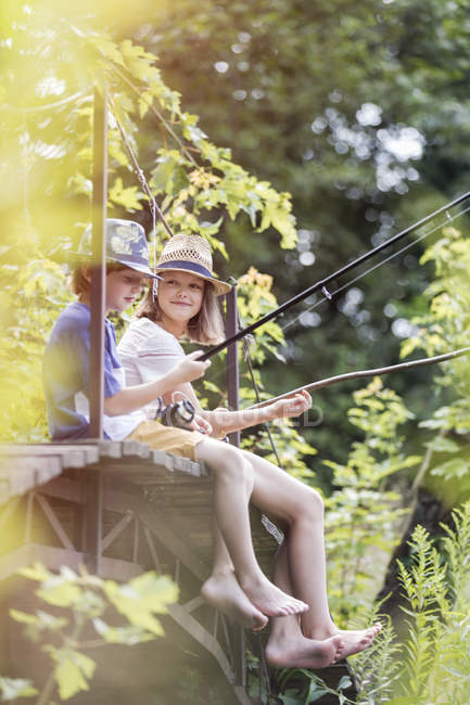 Хлопчик і дівчинка сидить і риболовлі — стокове фото