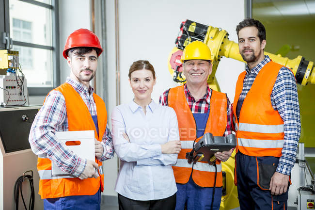 Portrait of confident staff in factory with industrial robot in background — Stock Photo