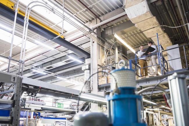Мужчины, стоящие на заводе — стоковое фото
