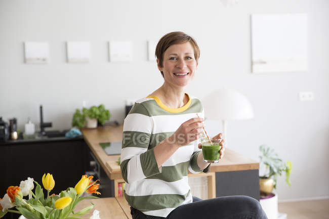 Woman with green smoothie in kitchen — Stock Photo