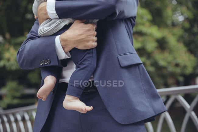 Homme d'affaires détenant bébé garçon — Photo de stock