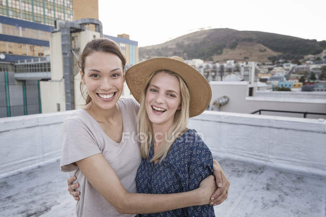Friends embracing on rooftop — Stock Photo