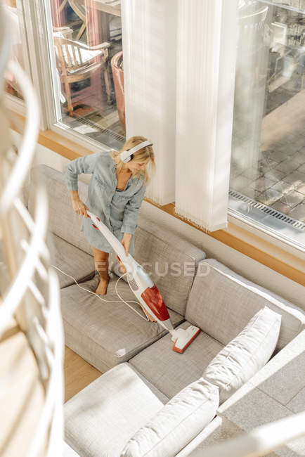 Woman hoovering couch — Stock Photo