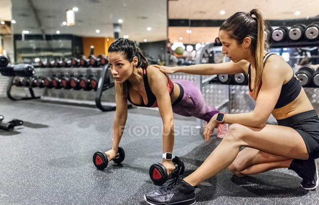 Woman with trainer working out in gym — Stock Photo