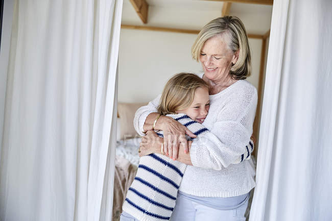 Grandmother hugging granddaughter — Stock Photo