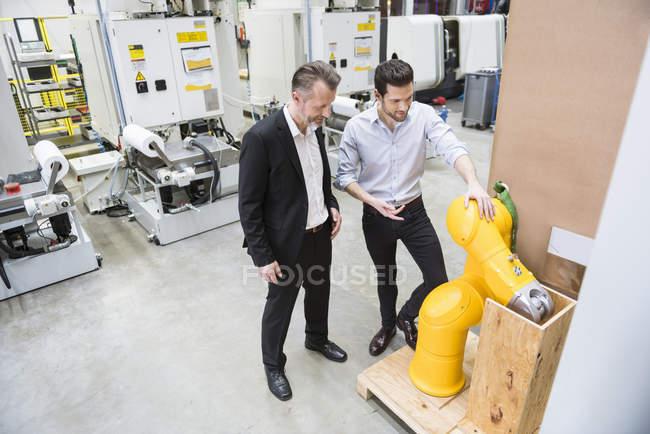 Men examining industrial robot — Stock Photo