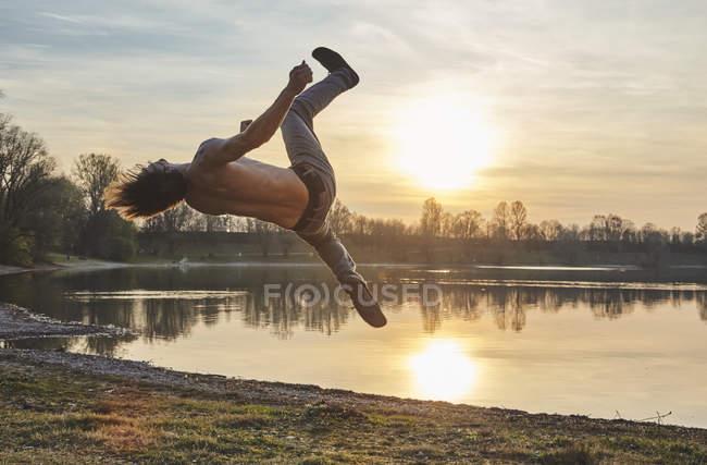 Germania, Baviera, Feldkirchen, uomo che fa parkour a lakeshore — Foto stock