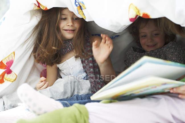 Children with book under blanket — Stock Photo