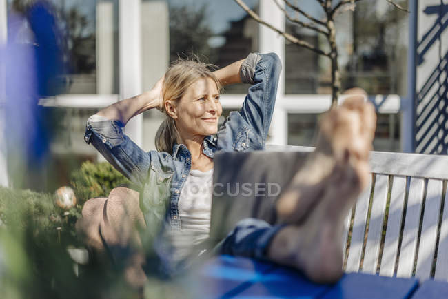 Woman with laptop relaxing on garden bench — Stock Photo