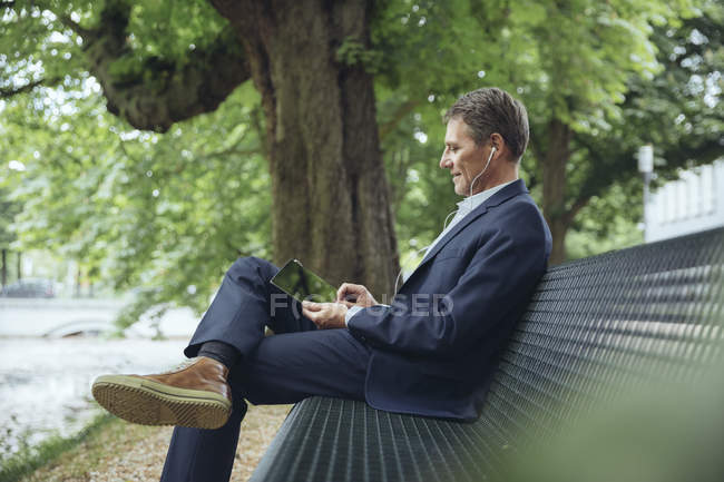 Бизнесмен, сидя на скамейке в парке — стоковое фото
