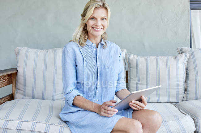 Woman sitting on couch with tablet — Stock Photo