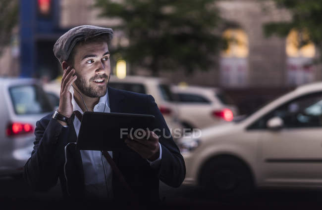 Man using tablet with earphones — Stock Photo
