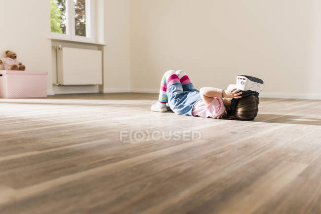 Girl in empty apartment wearing virtual reality glasses — Stock Photo