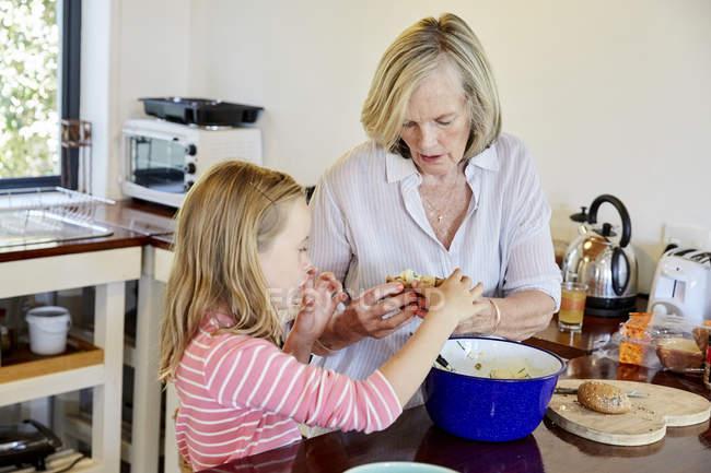 Grandmother and granddaughter preparing food — Stock Photo