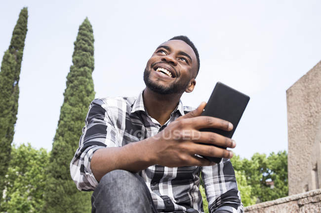 Happy young man with cellphone — Stock Photo