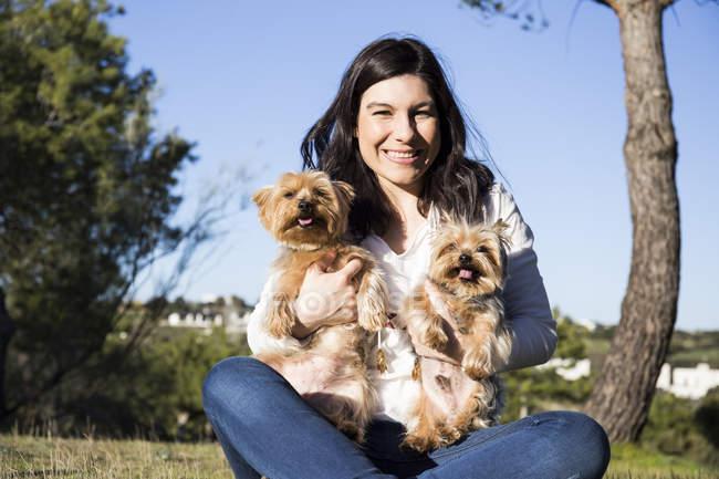 Mujer sentada con Yorkshire Terriers - foto de stock