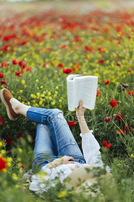 Woman lying in field and reading book — Stock Photo