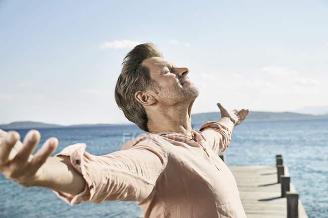 Людина на jetty з зброї outstreched — стокове фото