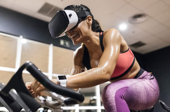 Woman with VR glasses on spinning bike — Stock Photo
