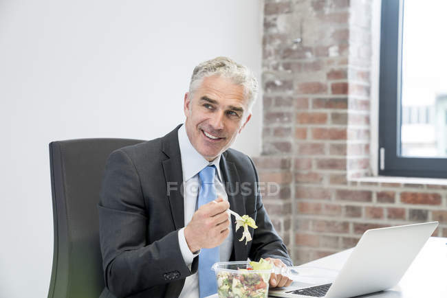 Businessman eating salad — Stock Photo