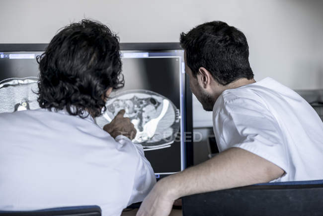 Two doctors discussing x-ray image on computer screen — Stock Photo