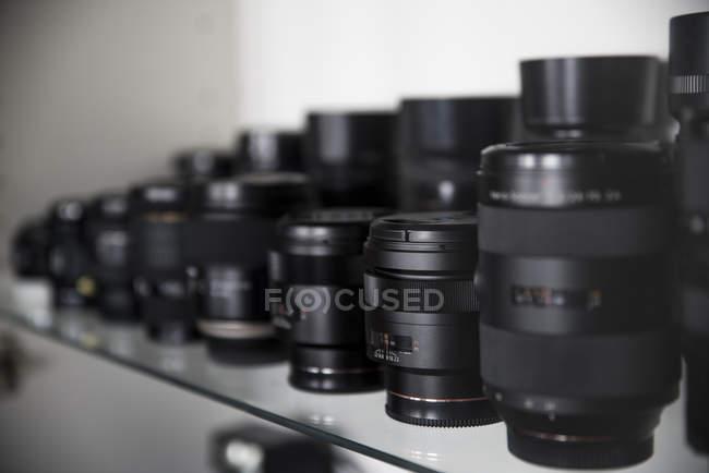 Sammlung von Objektiven für Spiegelreflexkameras auf Glasregal — Stockfoto