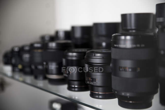 Collection of lenses for reflex cameras on glass shelf — Stock Photo