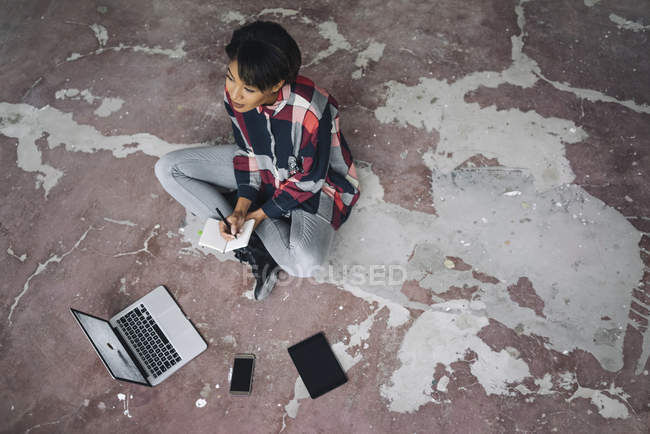 Woman sitting on floor with notebook — Stock Photo