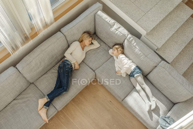 Woman and girl lying on couch — Stock Photo