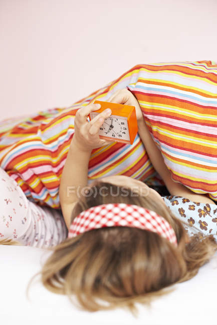 Girl in bed setting the alarm clock — Stock Photo